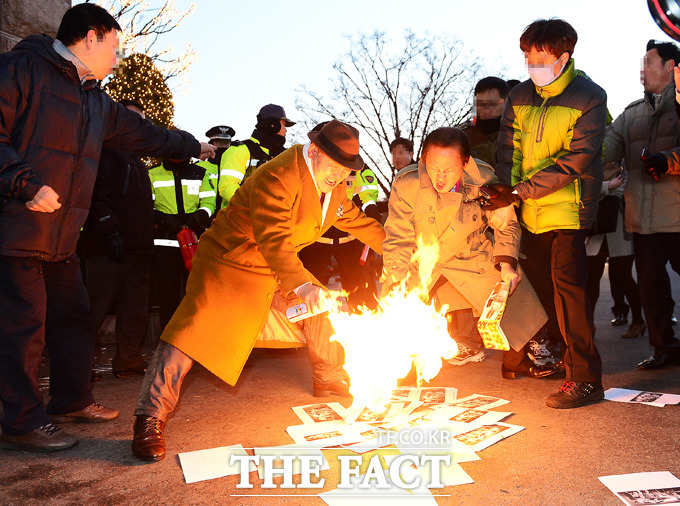 일왕 생일 축하행사를 반대하는 시민단체 애국국민운동대협회가 미리 준비한 전단지에 불을 붙이고 있다./하얏트호텔= 배정한 기자