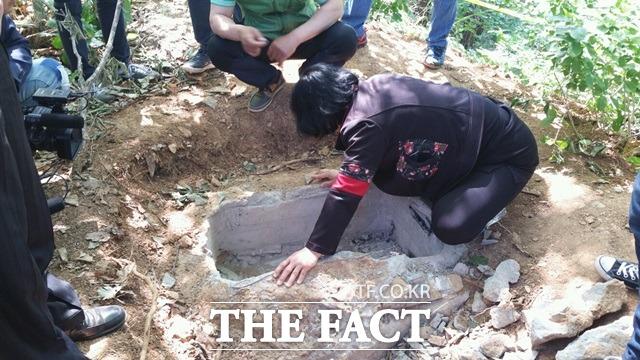 딸아, 얼마나 아팠니 지난 26일 충북 제천의 한 야산에서 진행된 현장검증 전 피해자의 어머니가 딸이 묻혔던 장소를 들여다보고 있다./충북 제천=오경희 기자