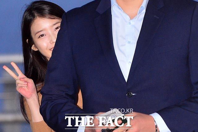 가수 아이유가 28일 오후 종영한 KBS2 드라마 프로듀사의 중국 홍보 활동을 위해 인천국제공항에서 중국으로 출국하는 가운데 경호원 뒤에서 포즈를 취하고 있다./인천국제공항=남윤호 기자