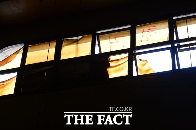 상인이 보는 하늘 어두컴컴한 시장에서 하늘을 올려다보면 오래된 창에 철거라는 표시가 돼 있다.
