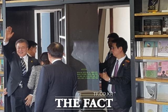 문 후보가 행사 후 회전문 뒤로 들어가며 지지자들에게 인사하고 있다.