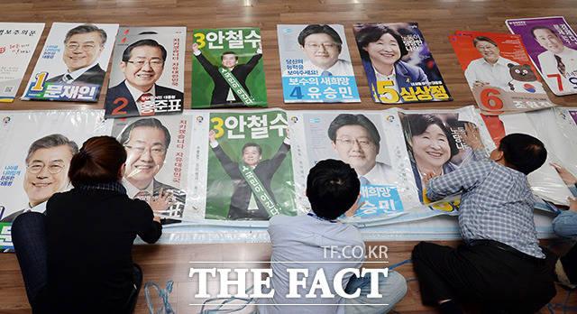 <b>대선 D-19 후보자 포스터 부착 </b>제19대 대통령 선거를 19일 앞둔 20일 오후 서울 가산동주민센터 직원들이 벽보를 부착하고 있다./임영무 기자