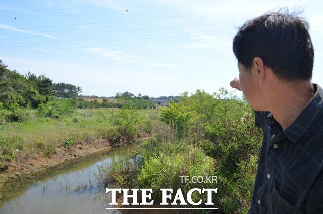 현대건설과 토지를 놓고 분쟁 중인 김 모 씨가 자신의 땅을 손으로 가리키고 있다. 김 씨는 현대건설이 만든 수로가 자신의 땅을 무단 점거했다며 원상복구를 요구하고 있다. /태안=장병문 기자