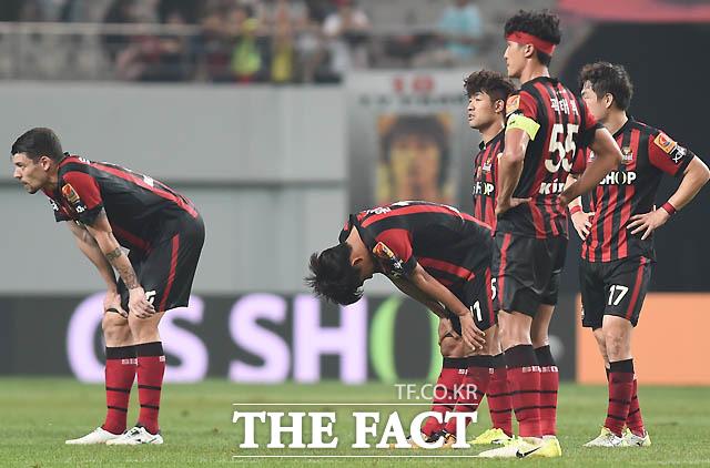 1-2로 패한 서울 선수들이 고개를 숙이며 경기장을 빠져 나가고 있다.