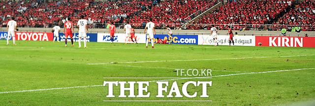 한국-이란전, 관중석의 팬들이 패여있는 잔디를 불안한 표정으로 지켜보고 있다.