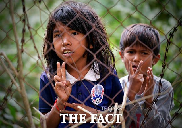 V가 아닌 2달러 지난 21일(현지시간) 캄보디아에 있는 킬링필드 유적지에서 아이들이 철조망 너머로 여행객에게 돈을 구걸하고 있다. /이덕인 기자