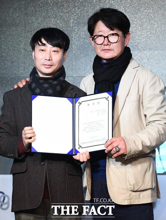 정병진 코리아닷컴 본부장(왼쪽)이 화가 김중식에게 조직위원회 부위원장 위촉장을 전달하고 있다.