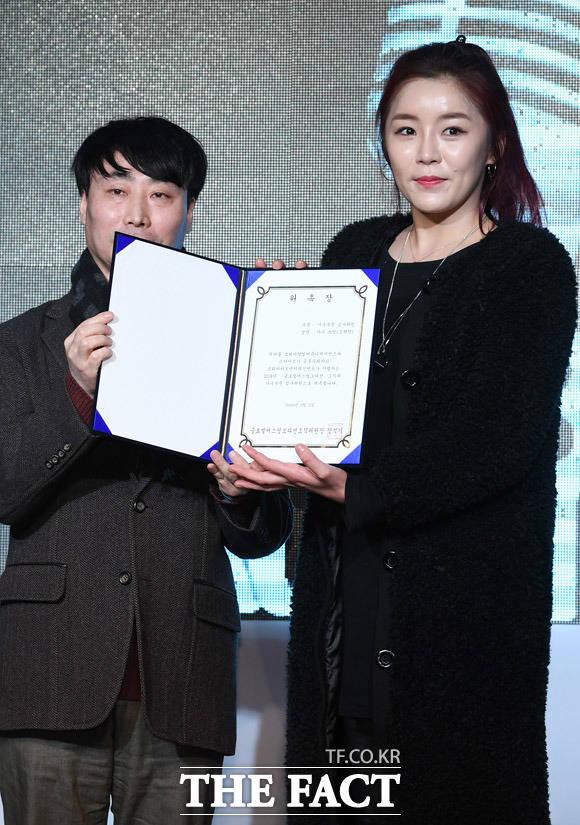 정병진 코리아닷컴 본부장(왼쪽)이 가수 쏘킴(김현민)에게 가수부문 심사위원 위촉장을 전달하고 있다.