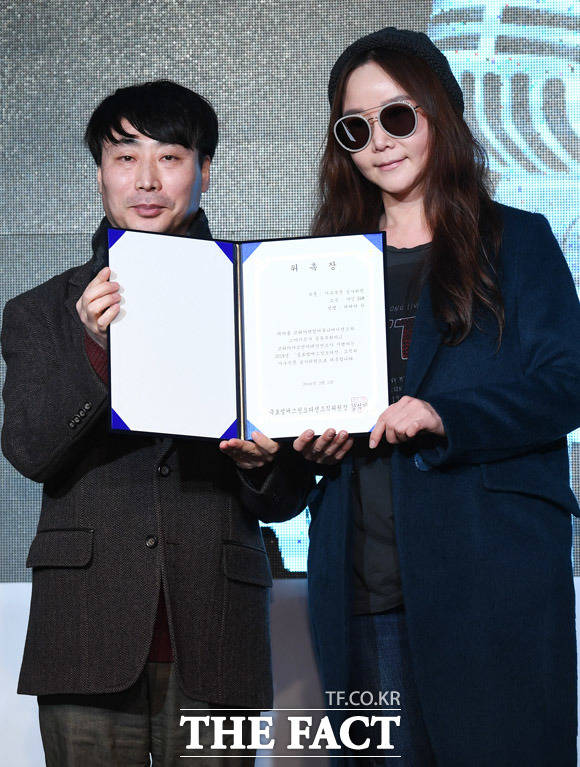 정병진 코리아닷컴 본부장(왼쪽)이 레베카한 샤인 E&M 대표에게 가수부문 심사위원 위촉장을 전달하고 있다.