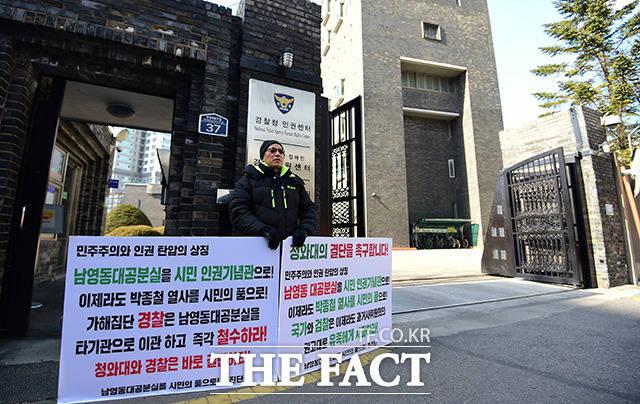 한 시민이 경찰청 인권센터 건물의 관리 권한 민간 이양을 촉구하는 시위를 진행하고 있다.