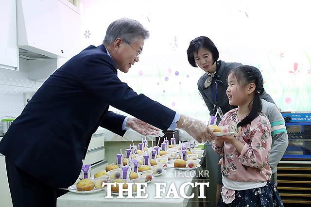 문재인 대통령이 4일 서울 경동초등학교에서 열린 온종일 돌봄 정책간담회에 앞서 돌봄교실에서 아이들에게 간식을 나눠주고 있다./ 청와대 제공