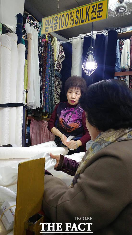 김정숙 여사가 지난해 12월 동대문 광장시장에서 원단을 고르는 사진./청와대 제공
