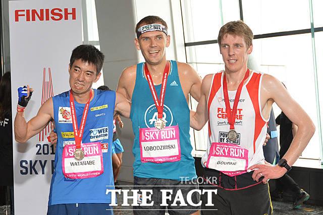 엘리트선수 남자부문 3위 료지 와타니베(일본)와 1위 피오트르 로보진스키(폴란드), 2위 마크 본(호주)(왼쪽부터)가 123층 결승선 통과 후 포토타임을 갖고 있다.