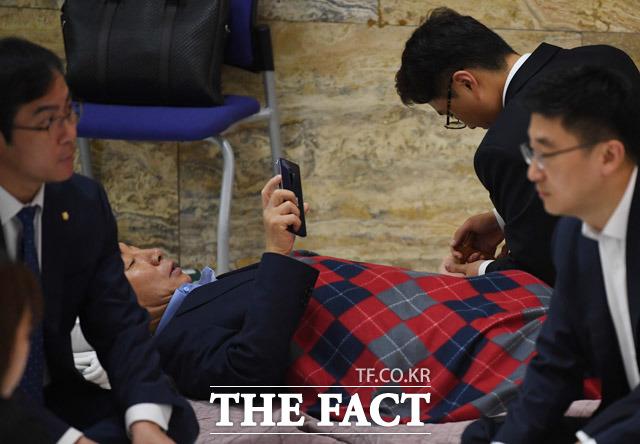 자유한국당 의원들이 14일 서울 여의도 국회의사당 본회의장 앞 로텐더홀에서 입구를 막은채 농성을 이어갔다. 병원에서 퇴원한 김성태 원내대표는 이날 농성장에서 지압을 받기도 했다. /배정한 기자