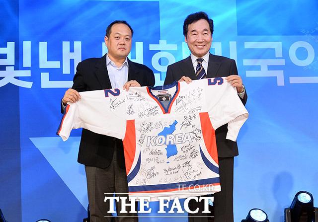이낙연 국무총리(오른쪽)가 김지용 선수단장으로부터 남북 아이스하키 단일팀 선수들의 사인이 새겨진 유니폼을 전달받고 있다