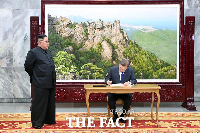 문재인 대통령이 26일 오후 판문점 북측 통일각에서 열린 남북정상회담에서 방명록에 글을 남기고 있다. 김정은 북한 국무위원장이 박수를 치고 있다./ 청와대 제공