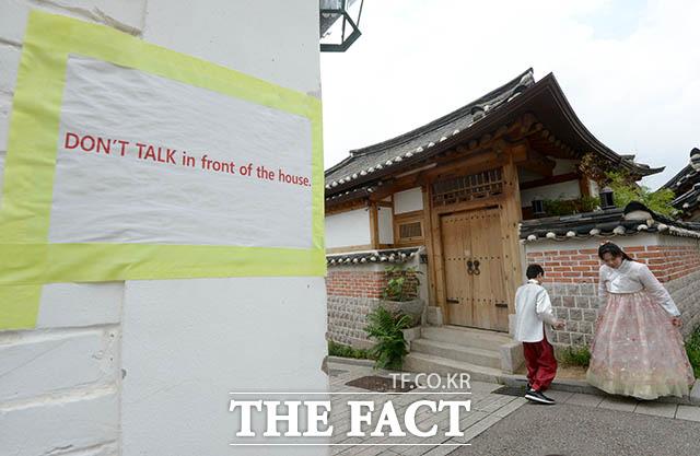 한 집 앞에는 영어로 집 앞에서 이야기하지 말아달라는 내용의 문구가 붙어 있다.