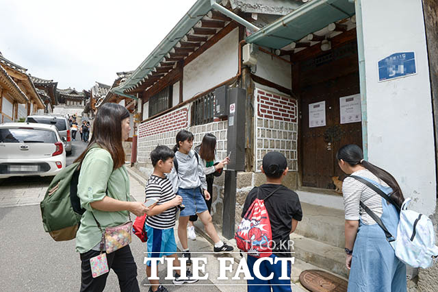 대문 앞 안내판에도 불구하고 집 앞에 모여 사진을 찍는 중국인 관광객들