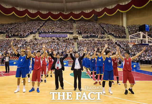 남측 허재 감독, 북측 리덕철 감독, 선수들이 관중을 향해 손을 흔들고 있다.