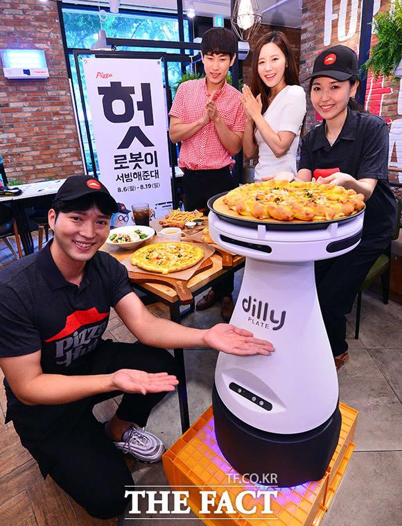 8일 오전 서울 양천구 피자헛 목동중앙점에서 직원과 모델들이 서빙 로봇 딜리 플레이트(Dilly Plate)를 선보이고 있다. /이동률 기자
