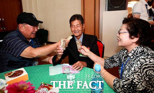 남측 함성찬 할아버지가 동생 함동찬 할아버지와 함께 과자를 나눠먹고 있다.
