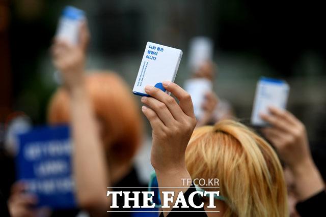 26일 오후 서울 종로구 보신각 앞에서 여성단체 페미당당 회원들이 낙태죄 폐지를 요구하는 집회에 참석해 임신중단 약물을 먹는 퍼포먼스를 진행하고 있다./남윤호 기자