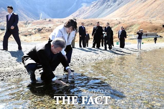 문재인 대통령이 20일 오전 김정은 국무위원장과 백두산 천지를 산책하던 중 천지 물을 물병에 담고 있다. /평양사진공동취재단