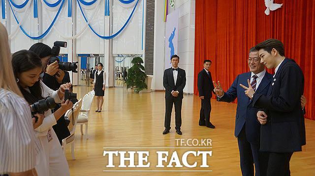 가수 에일리(왼쪽)가 포즈를 취한 문재인 대통령과 가수 지코(오른쪽)의 사진을 찍고 있다.