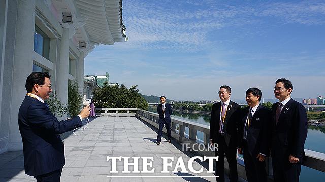 최태원 SK 회장이 구광모 LG 회장, 이재웅 쏘카 대표, 이재용 삼성전자 부회장(왼쪽부터)의 기념사진을 찍어주고 있다.