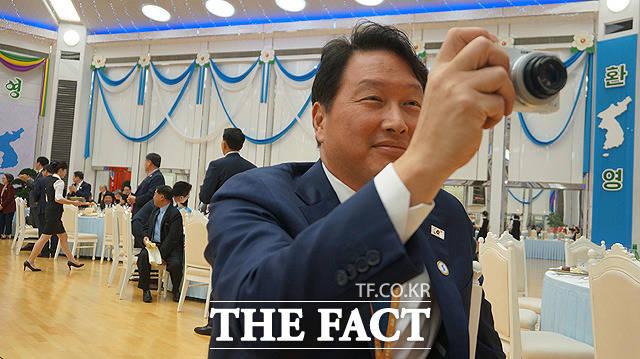 최태원 SK 회장이 디지털 카메라를 들고 사진을 찍고 있다.