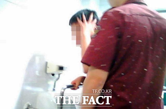 한 사회복무요원이 학교 화장실에서 장애 학생을 이리저리 끌고 다니며 폭력을 행사하고 있다. 겁에 질린 장애 학생은 주먹질을 피하려 손으로 머리를 막고 있다.