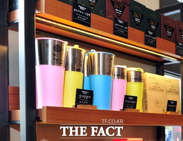텀블러 등 다회용컵이 자원재활용법 시행으로 커피 매장에서 매출이 크게 늘어난 것으로 나타났다.  한 커피 매장 상품 진열장에 비치된 텀블러 모습. / 뉴시스