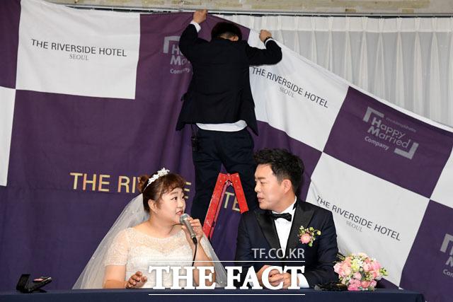 17일 오후 서울 강남구 더리버사이드호텔에서 결혼식을 앞둔 개그우먼 홍윤화(왼쪽)와 김민기가 기자회견에 참석해 취재진의 질문에 답변하는 가운데 호텔 관계자가 현수막을 걸고 있다./남윤호 기자