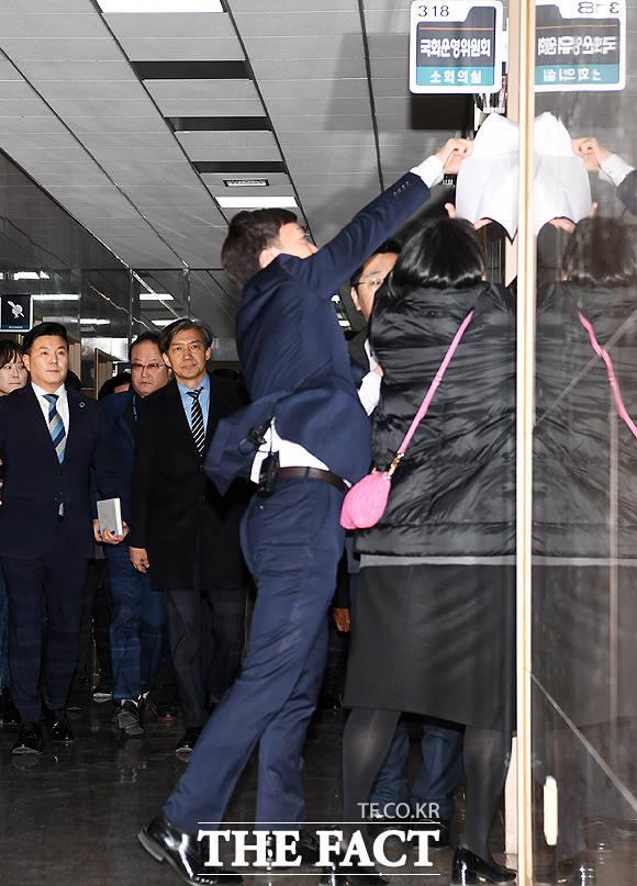 조국 청와대 민정수석(왼쪽 세번째)이 31일 서울 여의도 국회의사당에서 열리는 운영위원회 전체회의에 출석하기 위해 이동을 하던 중 인지연 대한애국당 수석대변인(오른쪽)의 피켓 시위를 지켜보고 있다. / 국회=이새롬 기자