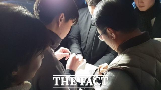 홍준표(오른쪽) 자유한국당 전 대표가 18일 TV홍카콜라 1000만 조회 기념 생방송을 마친 뒤 기다린 청년 지지자에게 사인해주고 있다. /이원석 기자