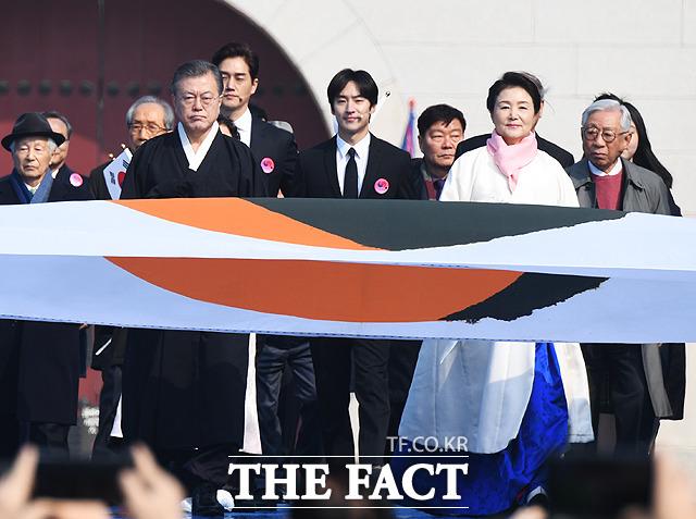 관사 태극기와 함께 입장하는 문재인 대통령(왼쪽)과 김정숙 여사