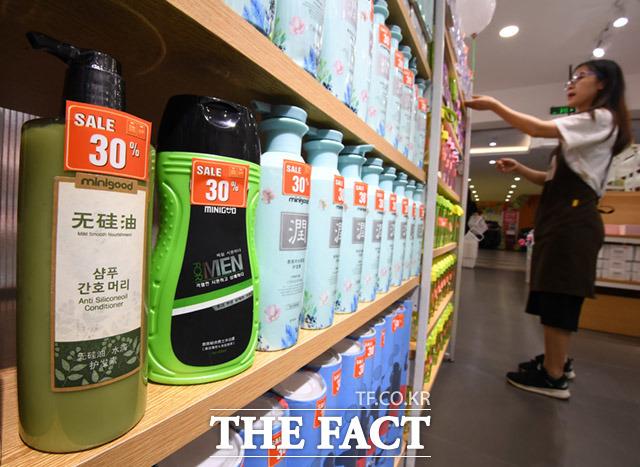 점원이 매장을 관리하는 가운데 한글이 적힌 샴푸 제품이 보이고 있다.