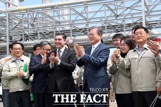 문재인 대통령과 구르반굴리 베르디무하메도프 투르크메니스탄 대통령이 18일(현지시각) 투르크멘바시 키얀리 가스화학플랜트 공장을 방문해 근로자들과 기념촬영을 한 뒤 박수를 치고 있다. /청와대 제공