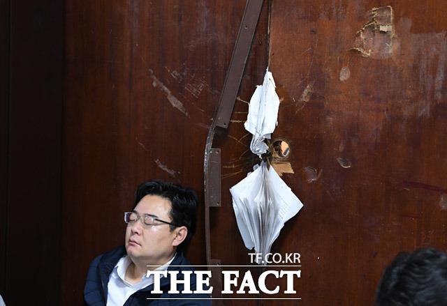 김성원 의원이 기대고 있는 의안과 출입문이 파손돼있다.