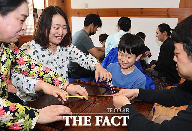 장수를 상징하는 오색실을 꼬아 '오색 장명루(長命縷)' 를 만드는 가족들
