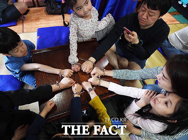 어린이날인 5일 서울 남산공원 호현당을 찾은 가족들이 화합과 협력의 의미를 새겨보며 만든 오색 장명루 팔찌를 선보이고 있다. /이새롬 기자