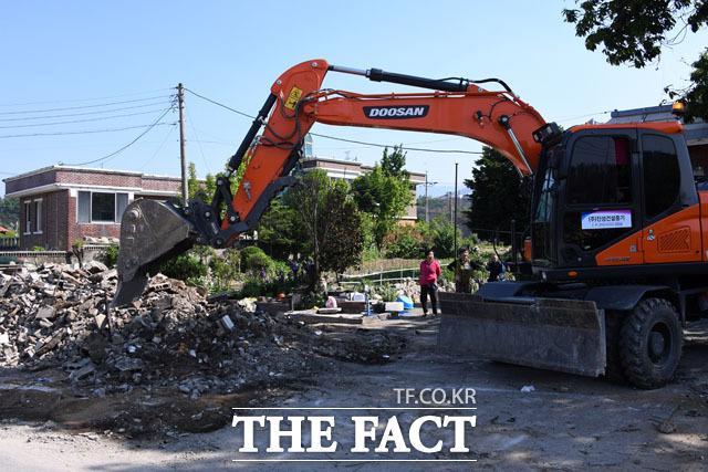 철거 바라보는 주민들 철거 잔해물을 무덤덤하게 바라보는 마을 주민들. 철거 작업이 끝나면 기다렸다가 포클레인과 함께 다음 철거 장소로 이동한다.