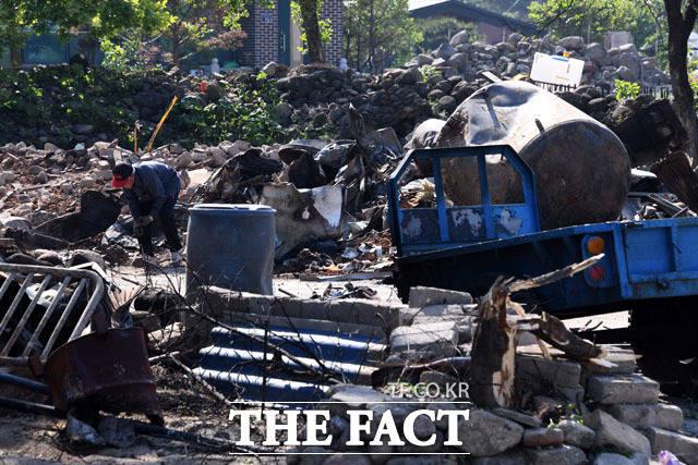 살림 하나라도... 화재로 집을 잃고 철거를 마친 노인이 잔해물 속에서 공구를 찾아 들고 있다.