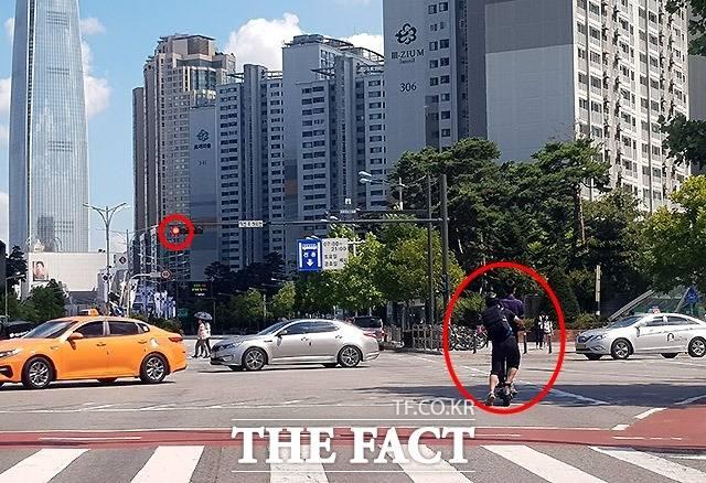 불안한 동행 16일 서울 송파구 석촌동 일대에서 전동킥보드를 탄 한 남성과 여성이 빨간불 신호를 지나쳐 교차로를 지나고 있다. 뒤에 있던 여성이 도로에 다리를 내딛는 상황이 불안해 보인다.