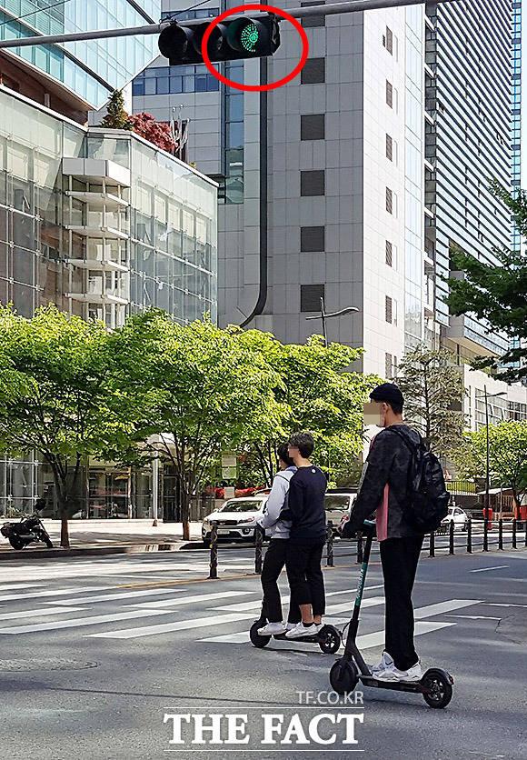 교차로 신호 무시 2일 서울 마포구 상암동에서 직장인들이 교차로 신호를 무시하고 전동 킥보드를 운전하고 있다. 2명이 한대를 타고 이동하는 모습도 위험해 보인다.