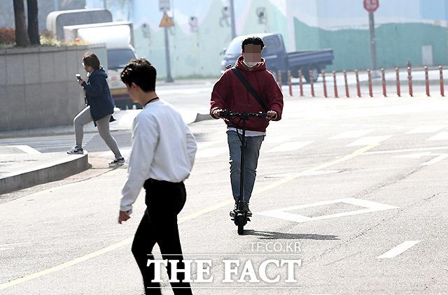 사람들 사이로 쌩썡~ 한 직장인 남성이 보행자 사이로 전동 킥보드를 운전하며 차로를 역주행하고 있다. 2일 서울 마포구 상암동 중소기업DMC빌딩 앞.