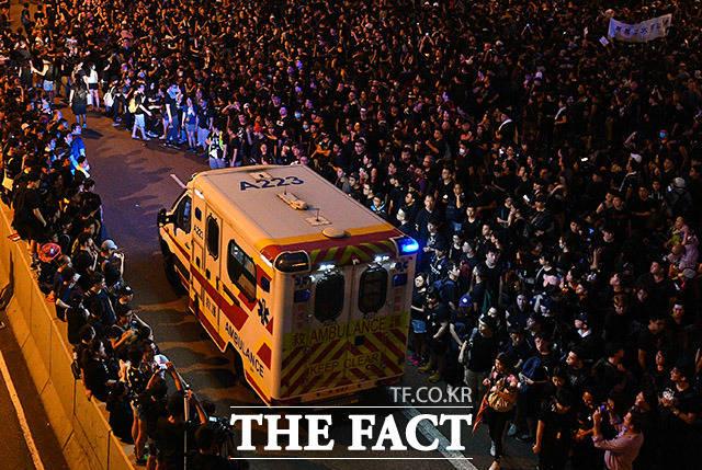 구급차가 지나갈 길을 터주는 시위대