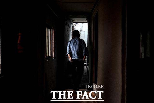 18일 서울 용산구 동자동의 한 쪽방촌에서 한 주민이 어두운 쪽방을 지나고 있다. 누구나 겪을 수 있는 가족과 사회의 단절, 고독사는 이러한 단절 속에 찾아오는 슬픈 말로다. /임세준 기자