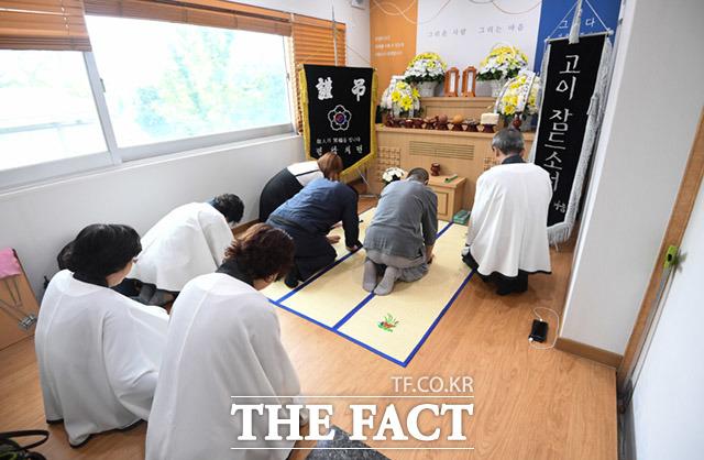 고인을 기리는 봉사자들의 기도.
