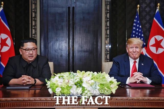 김 위원장과 트럼프 대통령이 지난해 6월 싱가포르 센토사 섬 카펠라호텔에서 열린 북미정상회담 공동합의문 서명식에서 사인을 마친 뒤 카메라를 바라보고 있다.트럼프 대통령은 웃음을, 김 위원장은 옅은 미소를 띄고 있다. /싱가포르 통신정보부 제공